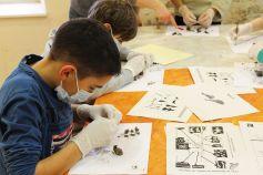 Les enfants jouent aux petits scientifiques pour disséquer une pelote de réjection
