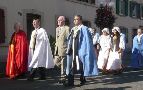 Fête des Ménétriers à Vieux Thann : les ménétriers vont escorter leur nouveau roi, cierge à la main sur le chemin de l\'église Saint-dominique