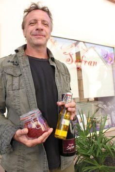 Hervé Barbisan et ses déclinaisons de produits au safran, devant sa boutique de Saint-Hippolyte