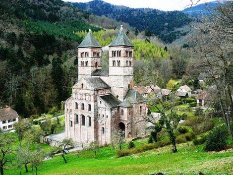 La façade de l'abbaye de Murbach surgit parmi la forêt des Vosges
