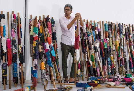 Manish Nai, artiste indien, aux côtés de ses œuvres en tissus collés